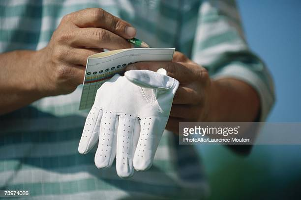 Golfer noting score, close-up of hands