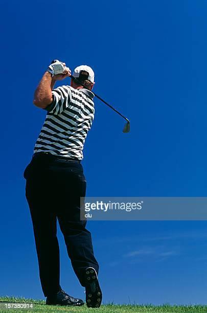 青い空を背景にゴルフプレー