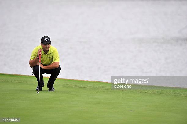 US golfer Patrick Reed lines up his putt on the 1st green in his match against Swedish golfer Jonas Blixt during the first day of World Match Play...