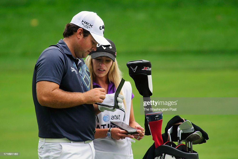 Golfer Patrick Reed talks with his wife, Justine Karain, who serves as his caddy at the 11th hole of the Congressional Country Club golf course during the AT&T National Golf Tournament in Bethesda, MD, on June 27, 2013.