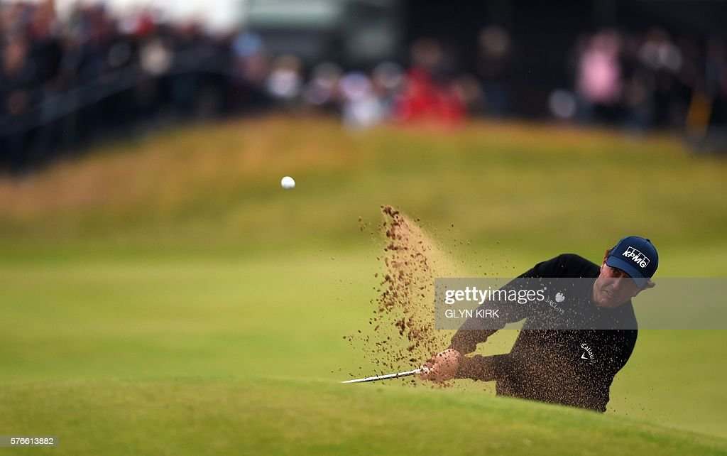 US golfer Phil Mickelson plays from a green-side bunker on the 18th hole during his third round 70 on day three of the 2016 British Open Golf Championship at Royal Troon in Scotland on July 16, 2016. Sweden's Henrik Stenson leads the British Open by a single shot from Phil Mickelson after the third round following his superb 68 on Saturday. Stenson, bidding to win his first major at the age of 40, had five birdies and two bogeys in his three-under-par round to move to 12-under for the championship. USE