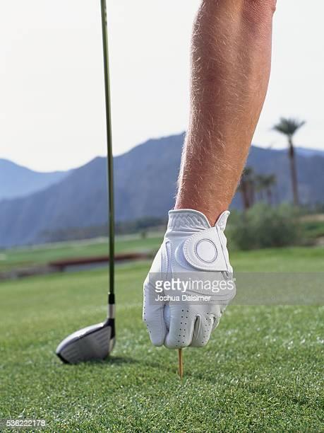 Golfer placing golf ball on golf tee