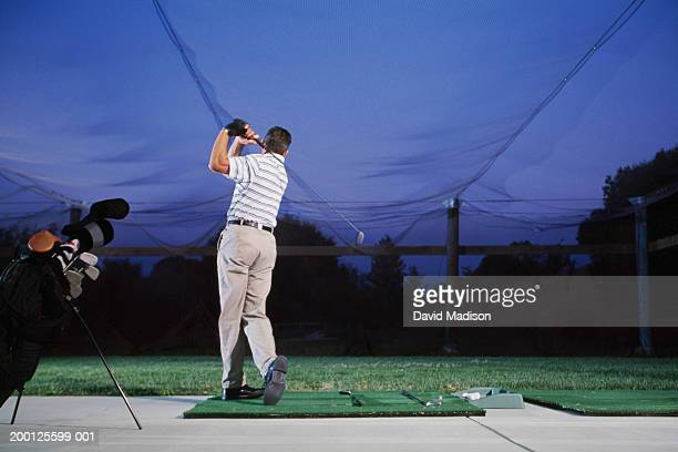 Golfer practicing at driving range, rear view
