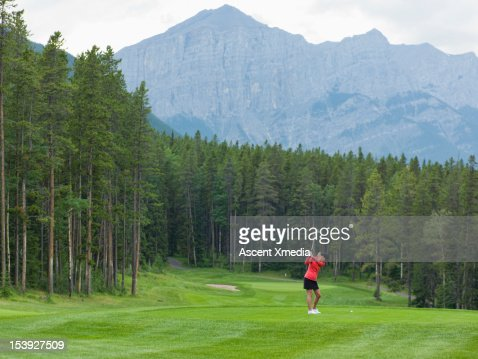Golfer prepares to drive ball down fairway, mtns : Stock Photo
