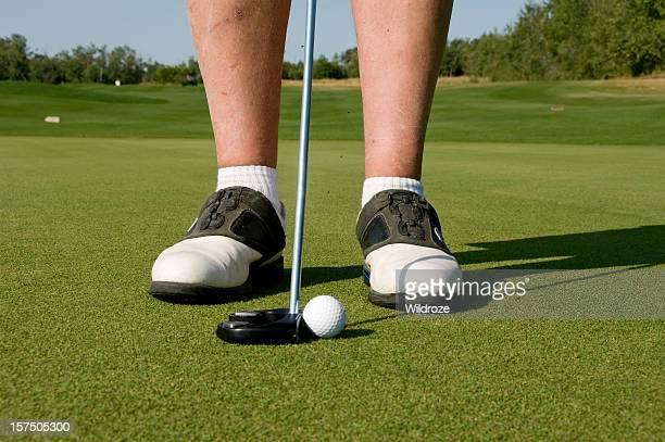 Golfer prepares to putt ball on greens