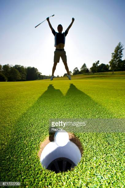 A Golfer raises his arms in celebration.