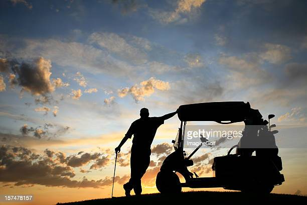 Golfspieler sich auf Golfwagen bei Sonnenuntergang
