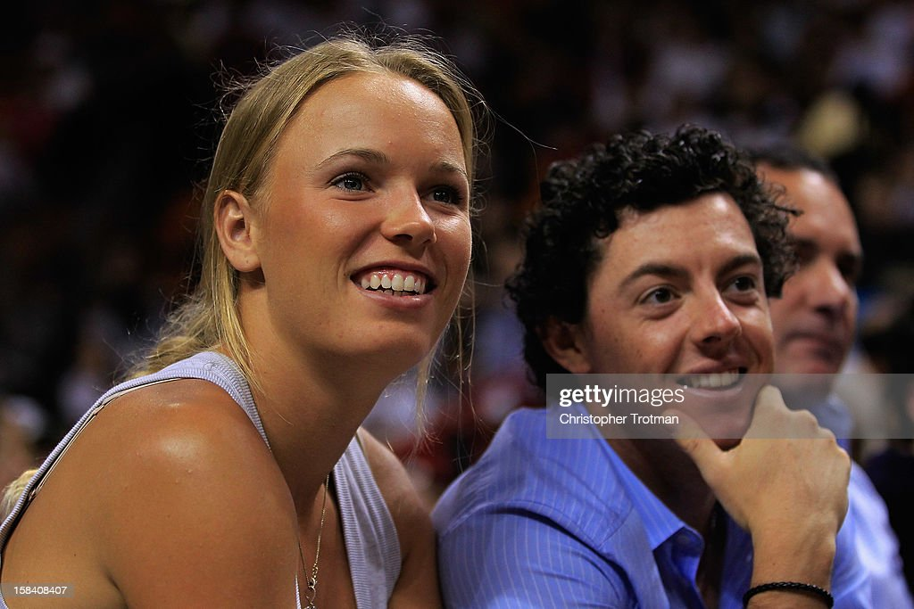 Golfer Rory McIlroy of Northern Ireland and (L) his girlfriend, tennis player, Caroline Wozniacki of Denmark watch a NBA game between the Miami Heat and Washington Wizards at American Airlines Arena on December 15, 2012 in Miami, Florida.
