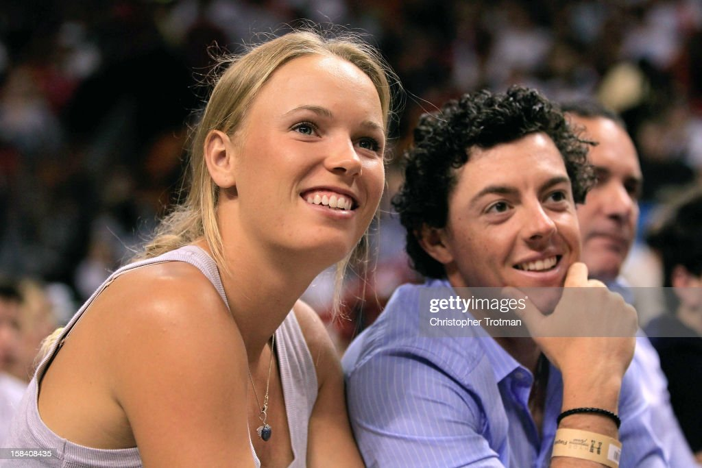 Golfer Rory McIlroy of Northern Ireland and (L) his girlfriend, tennis player, Caroline Wozniacki of Denmark watch an NBA game between the Miami Heat and Washington Wizards at American Airlines Arena on December 15, 2012 in Miami, Florida.