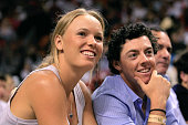 Golfer Rory McIlroy of Northern Ireland and his girlfriend tennis player Caroline Wozniacki of Denmark watch an NBA game between the Miami Heat and...