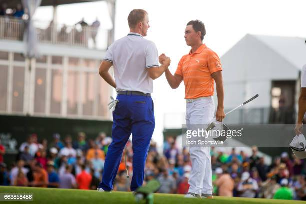 PGA golfer Russell Henley shakes hands with Rickie Fowler on the 18th green after Henley won the Shell Houston Open on April 02 2017 at Golf Club of...