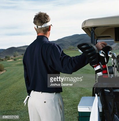 Golfer selecting golf club : Stock Photo
