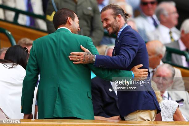 Golfer Sergio Garcia and David Beckham greet each other as Angela Akins looks on from the centre court royal box on day five of the Wimbledon Lawn...