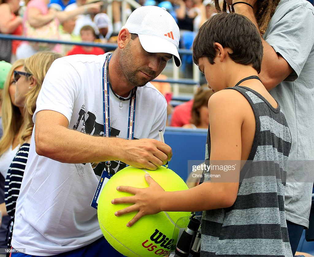 Golfer Sergio Garcia of Spain signs his autograph for a fan as James Blake of the United States and Lukas Lacko of Slovakia compete in their men's singles first round match during the 2012 U.S. Open at the USTA Billie Jean King National Tennis Center on August 27, 2012 in the Flushing neighborhood, of the Queens borough of New York City.