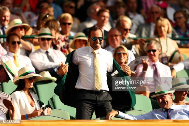 Golfer Sergio Garcia removes his green jacket in the centre court royal box on day five of the Wimbledon Lawn Tennis Championships at the All England...