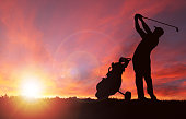 Silhouette of golfer and golf bag by his side swinging club toward sunset with deliberate lens flare and copy space. Sunset background image shot in Calgary (see attached). Silhouette created/drawn in