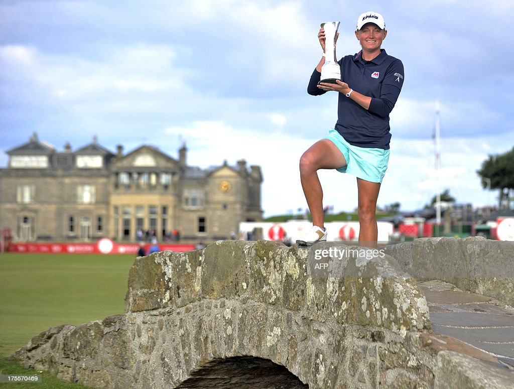 US golfer Stacy Lewis poses with the trophy on the Swilcan Bridge after winning the women's British Open Golf Championship at the Old Course in St Andrews, Scotland, on August 4, 2013. US golfer Stacy Lewis won the women's British Open on Sunday by two shots. Lewis, the winner of the 2011 Kraft Nabisco Championship, collected her second major with a final round 72 for an eight-under-par total of 280.