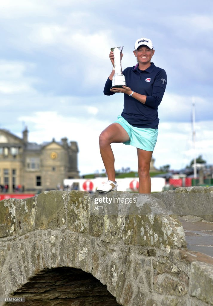 US golfer Stacy Lewis poses with the trophy on the Swilcan Bridge after winning the women's British Open Golf Championship at the Old Course in St Andrews, Scotland, on August 4, 2013. US golfer Stacy Lewis won the women's British Open on Sunday by two shots. Lewis, the winner of the 2011 Kraft Nabisco Championship, collected her second major with a final round 72 for an eight-under-par total of 280. AFP PHOTO/ANDY BUCHANAN