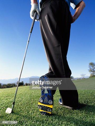 Golfer standing cross-legged : Stock Photo