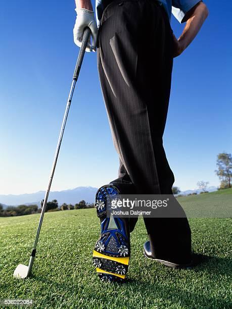 Golfer standing cross-legged