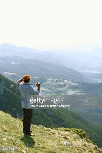 Golfer standing, overlooking mountainous landscape : Stock Photo