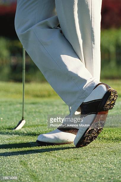 Golfer standing with ankles crossed, knee down