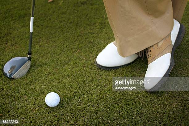 Golfer standing with golf ball and club