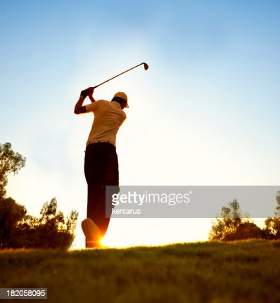 Golfer swinging at beautiful sunset