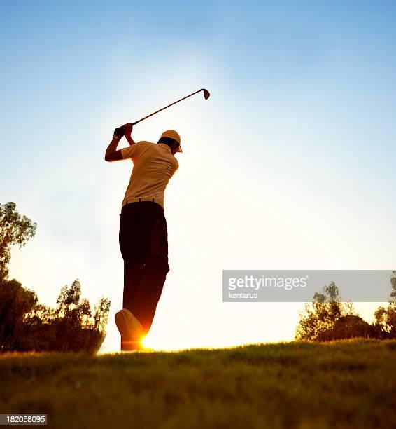 Golfspieler schwingen im wunderschönen Sonnenuntergang