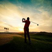 Golfer swinging at sunset