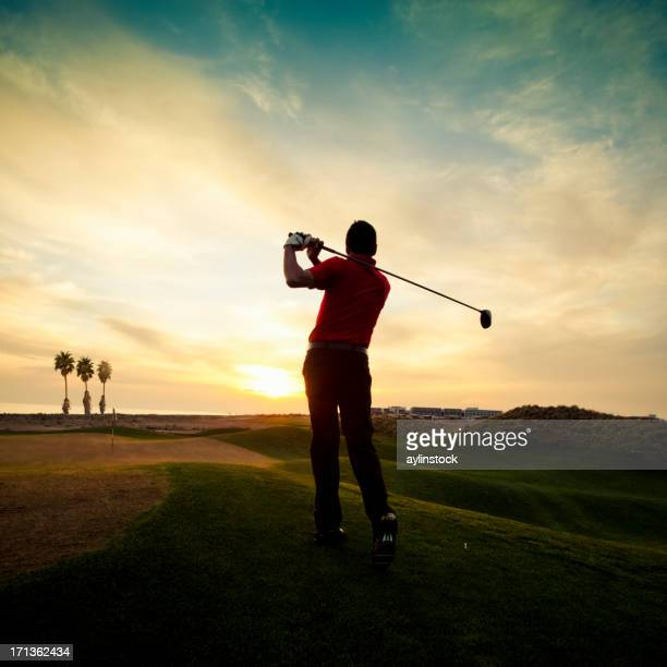 Golfer swinging at sunset
