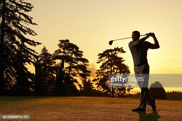 Golfer swinging club on golf course at sunset