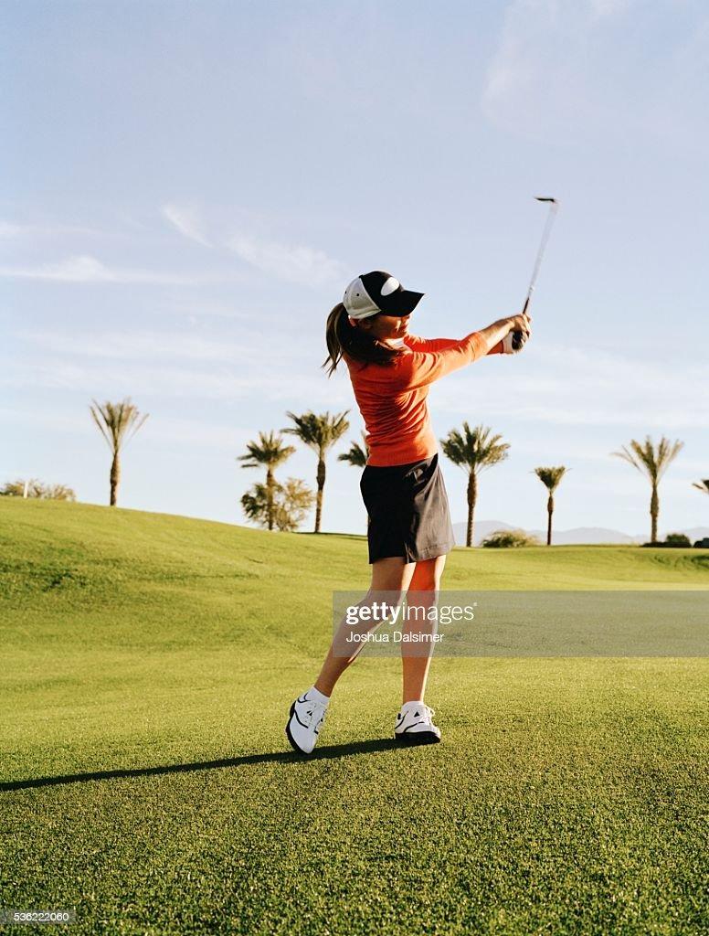 Golfer swinging golf club : Stock Photo