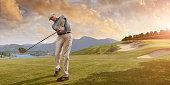 Golfer Swings at Sunset