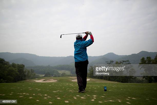 A golfer tees off on a golf course at Mission Hills Dongguan operated by Mission Hills Group Ltd in Dongguan Guangdong province China on Friday Dec...