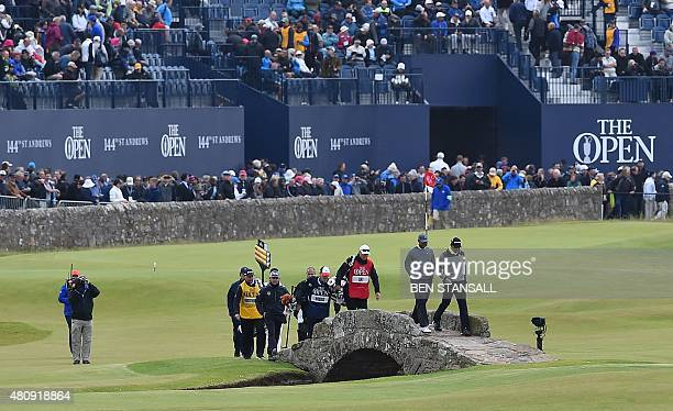 US golfer Tiger Woods and Australia's Jason Day walk over the Swilcan Bridge on the 18th hole during their first rounds on the opening day of the...