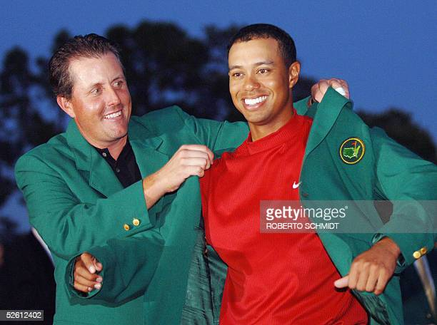 US golfer Tiger Woods is awarded his green jacket by 2004 champion Phil Mickelson of the US at the 2005 Masters Golf Tournament Championship 10 April...