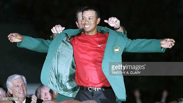 US golfer Tiger Woods is presented the green jacket by last year's winner Phil Mickelson of the US 10 April 2005 after Woods won the 2005 Masters...