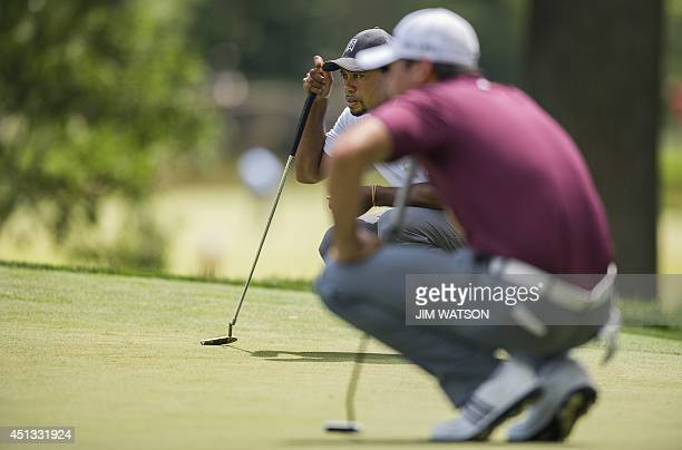US golfer Tiger Woods lines up his putt with Australian golfer Jason Day during the second round of the Quicken Loans National at Congressional...