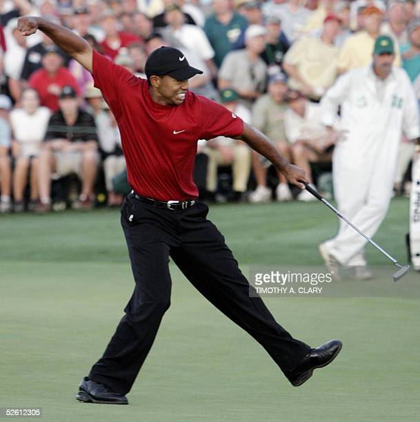 Golfer Tiger Woods of the US celebrates after making the winning putt on the 18th green 10 April 2005 during the final round of the 2005 Masters Golf...