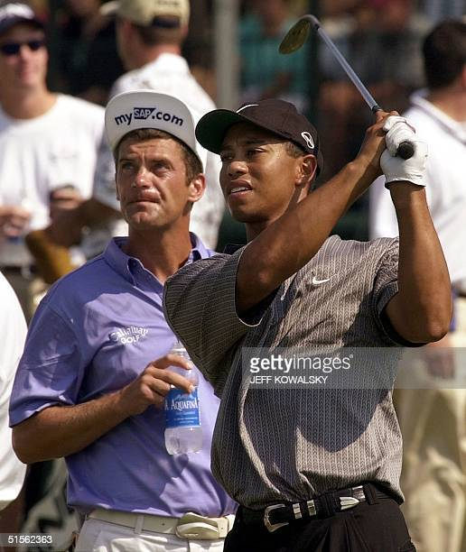 Golfer Tiger Woods of the US hits range balls from the practice area 15 August 2000 as fellow player Jasper Parnevik of Sweden looks on before the...