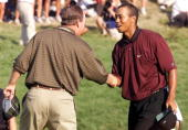 Golfer Tiger Woods of the US shakes hands with fellow countryman Bob May after their final putts on the 18th hole 20 August 2000 to force a playoff...