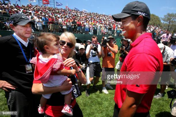 Golfer Tiger Woods right greets his wife Elin center and their daughter Sam foreground as his coach Hank Haney looks on after Tiger won the 108th US...