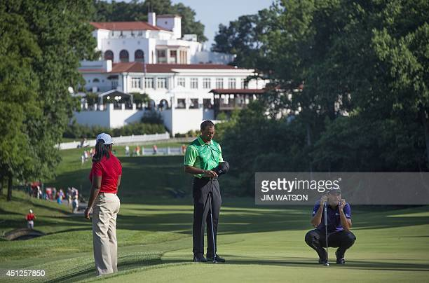 US golfer Tiger Woods stands on the 11th green with Australian golfer Jason Day during the first round of the Quicken Loans National at Congressional...
