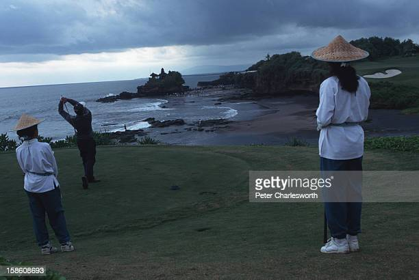 A golfer watched by two caddies drives across the beach towards the green He is playing the signature hole at the Greg Normandesigned Le Meridien...