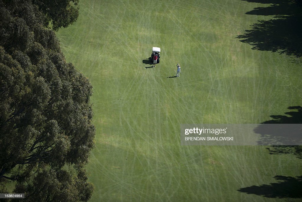 A golfer waves to a helicopter airlift as Marine One with US President Barack Obama flies over a course on October 7, 2012 in Los Angeles. Obama is on a three-day trip during which he will campaign in California and Ohio as well as attend the establishment of the Cesar Chavez National Monument. AFP PHOTO/Brendan SMIALOWSKI