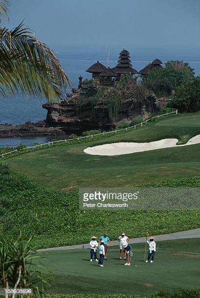 Golfers and caddies stand and putt on a green on the Le Meridien Nirwana Golf Spa Resort In the background is the seventh green the signature hole of...