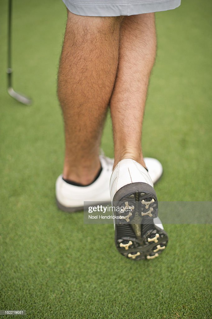 A golfer's cleats as he leans on his club : Stock Photo