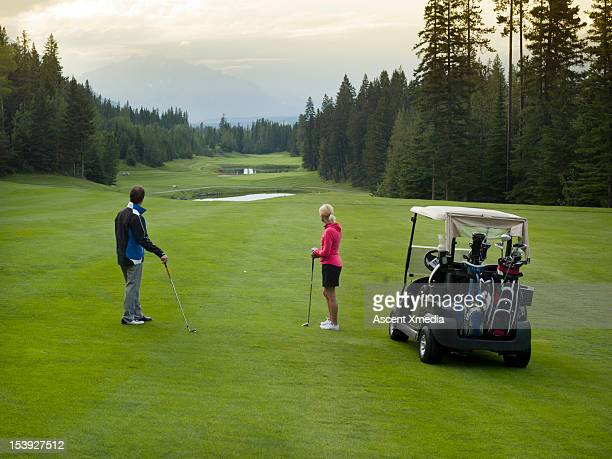 Golfers contemplate fairway and mountain view