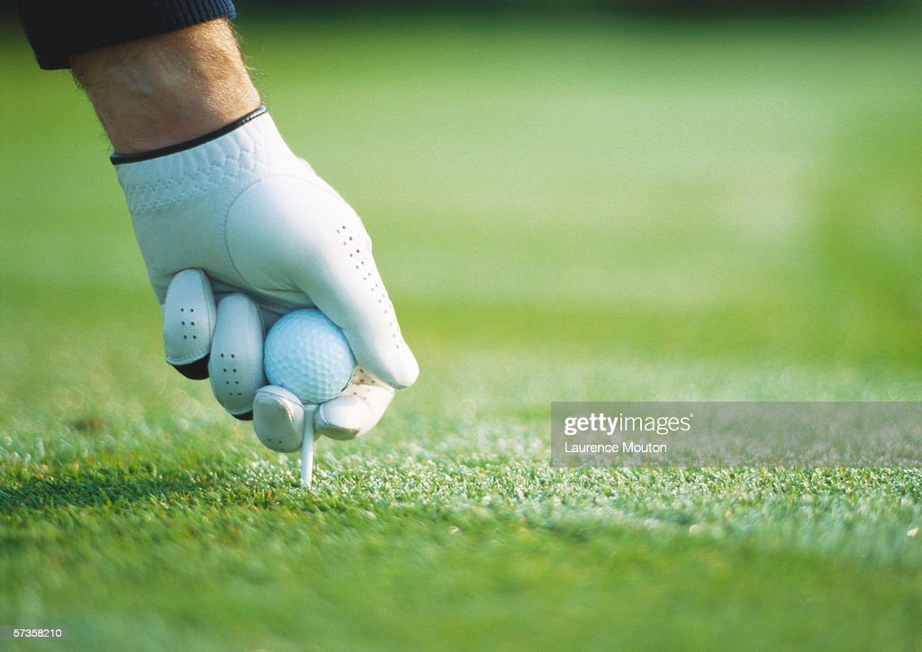 Golfer's gloved hand teeing up, close-up